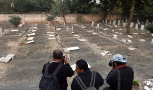 Reporters photograph the desecrated Ahmadi graves in Lahore. December 2012.